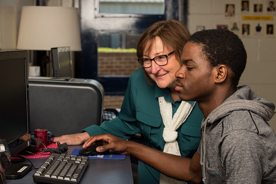 ACE Career Pathways Adviser Lisa Jones works with student to explore careers at a computer