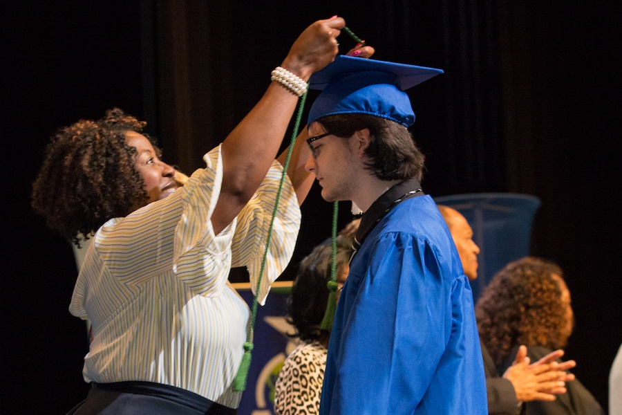 ACE Principal Browning presents cord to honor graduate