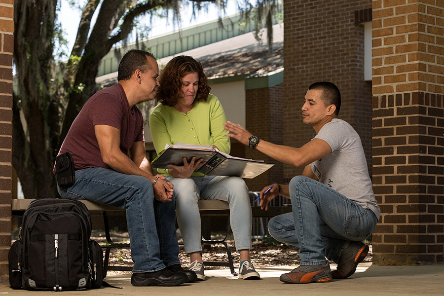 3 students talk in front of ACE Administration Building