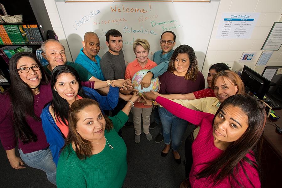 ACE ESOL Teacher Brenda Lee with globe and Hispanic students