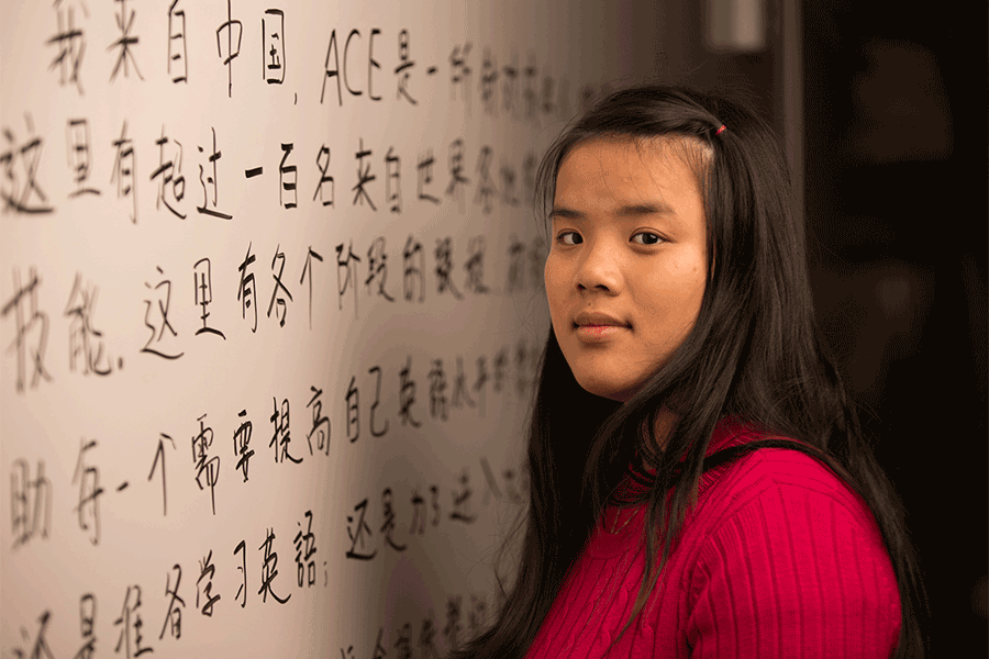 ACE English student in front of board with Chinese characters